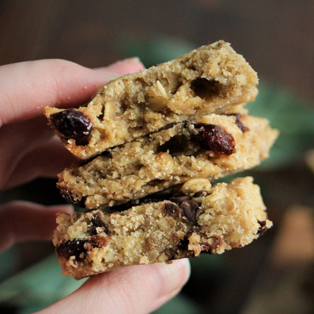 three cranberry-oat bars held in hand