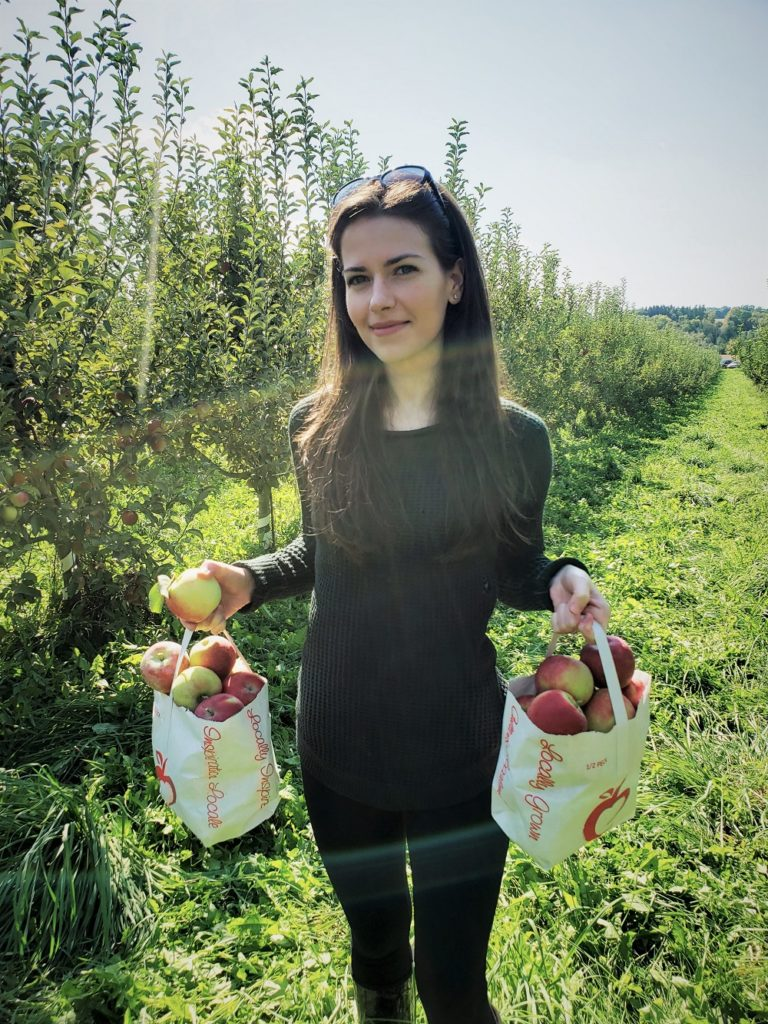 Fay apple picking while smiling at the camera