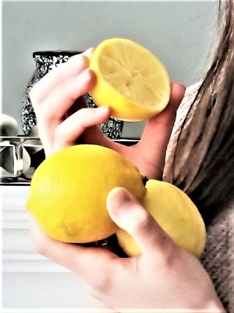 three lemons held in fay's hands