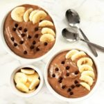 photo of two chocolate banana smoothie bowls topped with banana slices